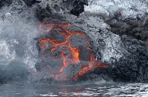 A lava flow cools along the shoreline and releases steam into the air on the Yemeni island of Jabal at-Tair.
