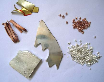 A photograph of assorted metals used for creating jewelry: scrap pieces of copper and brass, silver ingot, silver sheet, copper and germanium master alloy, fine silver granules.