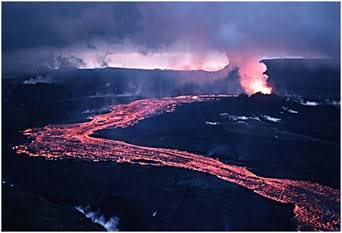 Photo shows a meandering stream of pink and yellow lava flowing down a hillside from a steaming volcano vent.