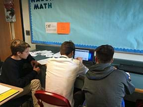 Three male students sit at a counter looking at a laptop screen showing the Desmos online graphing app.