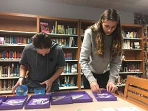 Two students are standing behind a table with six purple rectangular shallow bins containing stickers.  The student on the left is looking at the stickers they have placed in a giant plastic egg; the student on the right is using her hands to search for particular stickers.