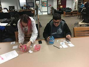 Two students are affixing face feature stickers onto large plastic Easter eggs.  A female student is standing and placing stickers onto a pink egg; a male student is sitting and placing stickers onto a blue plastic egg.