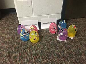 "Two signs entitled ""Product Warehouse"" are displayed.  In front of each sign are four plastic Easter eggs with face feature stickers affixed.  There is a purple, blue, yellow, and pink egg in each grouping."