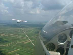 A photograph shows the view from inside an airborne glider: a glass-enclosed instrument panel, a rope connected to a small plane flying ahead of it, and green fields and blue sky beyond.