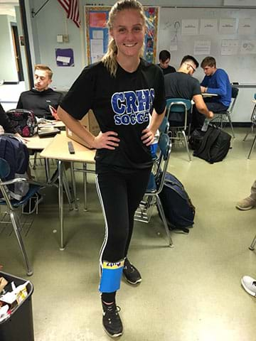 A female student models her cardboard shin guard.