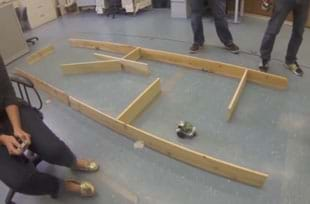 A photograph shows the legs of three teens watching and controlling a wheeled robot on a floor area of tiled linoleum to move through a maze made from long wooden boards positioned to stand on their thin edges to create low walls.