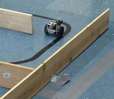 A photograph shows a wheeled robot on the floor navigating a maze made of wooden plank walls.