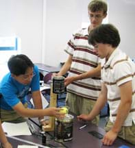 Photo shows three teenagers around a classroom table working on a device.