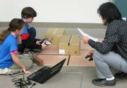 A photograph shows a teacher and two students around a maze on the floor made of boxes and tape lines. They are using a laptop and LEGO robot.