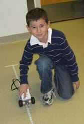 A photograph shows a young boy holding his LEGO robot on a tape measure line on the floor.