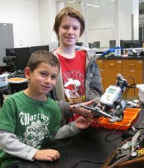A photograph shows two boys holding the LEGO robot they created.