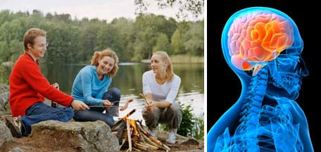 Photo shows three teens using sticks to roast hot dogs over the flames of a campfire by a lake. A blue x-ray-like image shows the shoulders, spinal cord and brain in a skull.