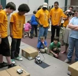 Students and teachers gather around a LEGO robot on a classroom floor along with various cardboard boxes.