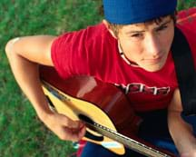 Photo shows a teen playing a guitar.