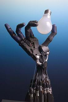 An image shows a dexterous robot hand and wrist, which appears to be delicately screwing in a light bulb.