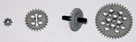 A photograph shows four plastic, multi-toothed disks with various small round cut-outs in their middle sections; one of these gears has a plastic axle through its center.