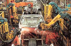 Photo shows car chassis moving through an automated assembly line, surrounded by robots performing welding and other tasks.