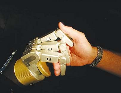 A photograph shows a handshake between a human hand and a robot hand.