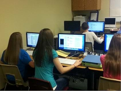 A photograph shows four students working at computers.