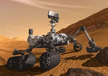An artists' illustration of a robot on wheels with a camera and sensors on a red-dirt surface of Mars.