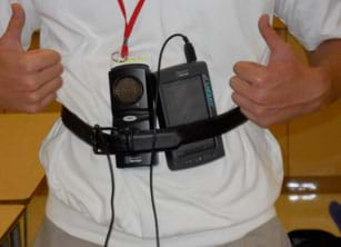 A photograph shows the activity's data collection setup, two palm-sized devices with cords (motion detector, accelerometer), both attached via belt to the middle front chest area of a teen.