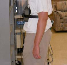 A photograph shows the same student as in Figure 1, viewed from the side, as he, and his strapped-on sensors, faces a wall/barrier.