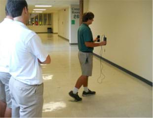 A photograph shows a student in a school hallway using an accelerometer to collect data on his gait.