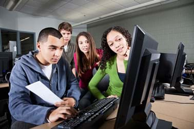 A photograph shows four teens around a computer, looking at the monitor and working on a project.