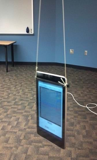 A photograph shows a seven-inch Android tablet computer hanging from a classroom ceiling via two strings attached at the top left and top right of the flatscreen device.