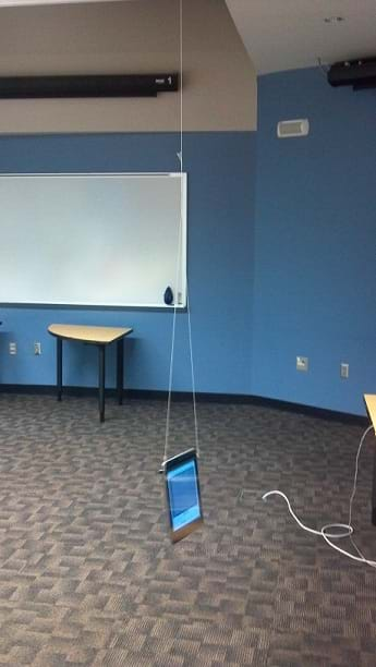 A photograph shows an Android tablet computer hanging from a classroom ceiling via two strings attached at the top left and top right of the flatscreen device. The tablet serves as a pendulum weight.