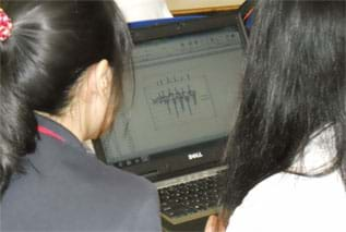 A photograph shows two girls looking at a graph on a laptop screen.