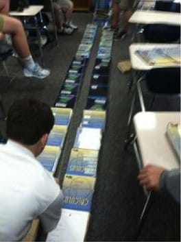 "Photo shows students on the floor with two long lines of textbooks about 10 cms apart. A student in the foreground holds one end of a rubber band string that runs the length of the textbook ""track."""