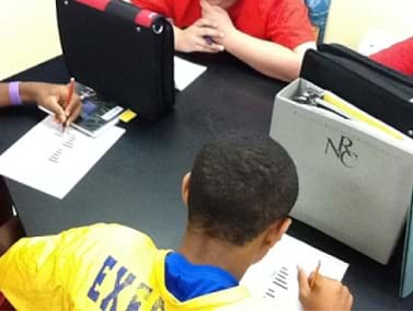 Photo shows students playing the game of battleship. Students have a sheet of paper in front of them and sit facing another student. Binders are placed on the table, standing vertically, between the students, so that students cannot see any other student's sheet of paper.