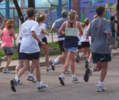 A photograph shows the backs of about 10 people in shorts and T-shirts jogging on a public street in a 5K race.