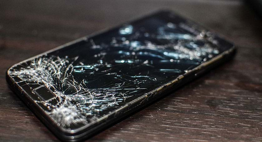 A photograph shows a Samsung Galaxy S2 cellular phone with a heavily cracked black glass display screen, the result of being run over by a Volvo tire.