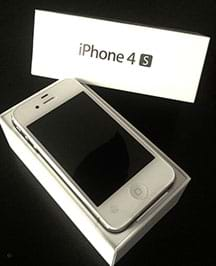 A photograph shows a rectangular white Apple iPhone 4s sitting in a white box with the box lid nearby; this is the original product packaging.