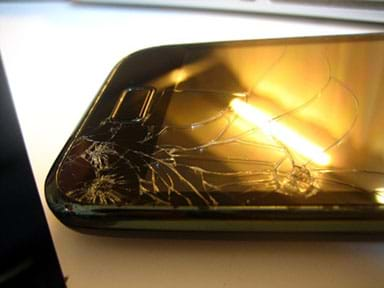 A photograph shows an iPhone with a cracked screen on a table with a ceiling lamp reflected in the glass.
