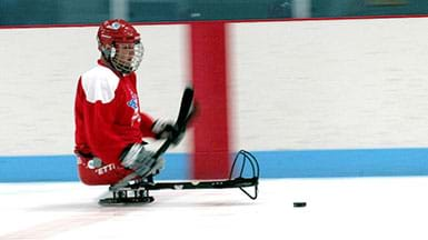 Sled hockey player on sled using hockey sticks to maneuver on the ice towards the puck.