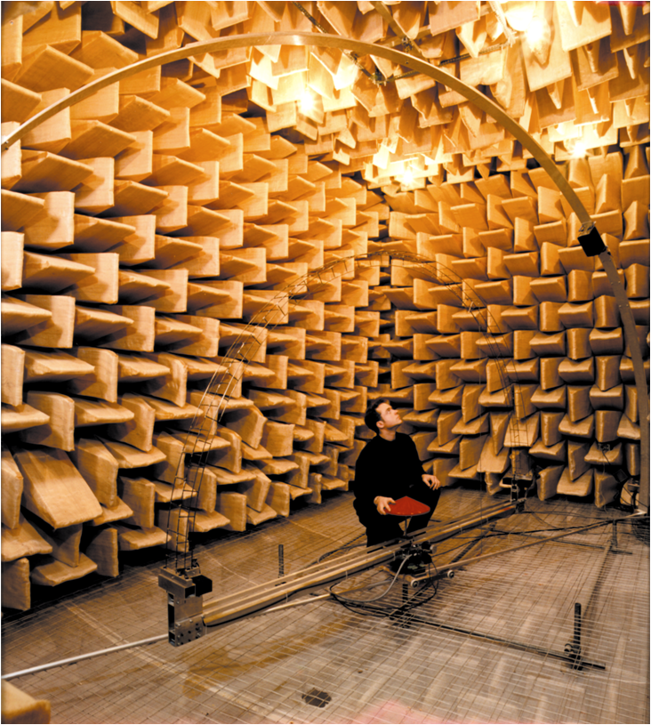 An acoustical engineer measures a sound instrument inside an anechoic chamber.