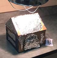 A photograph shows an illuminated clamp lamp positioned above what looks like a small, foil-covered cardboard peaked-roof house sitting on a laminate countertop. Nearby sits a thermometer.