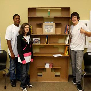 A photograph shows three teens standing next to a six-shelf bookcase that is taller than they are, which they designed and built of brown cardboard.