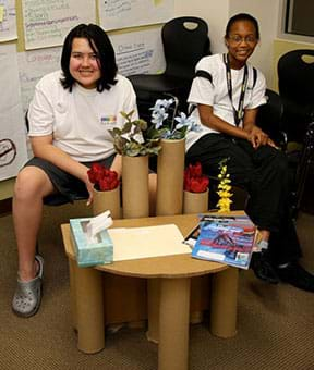 A photograph shows two girls sitting behind a low table that they designed and built of brown cardboard, including upright tubes holding flowers.
