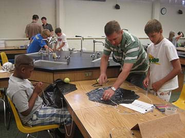 Image of a teacher standing at a counter in a science lab with two young students helping them create parachutes out of black plastic bags and string. The lab table is has supplies on it such as clipboards, paper, pens, tape and safety goggles.