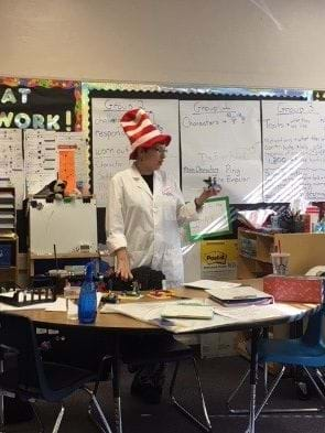 "A teacher stands behind a table of supplies, wearing a lab coat and a Dr. Seuss ""Cat in the Hat"" hat. She is holding her Lego kingdom. There are other Lego kingdoms on the table, along with the ""rain"" (A cup of water)."