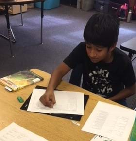 A male fifth grader sits at a table. He is writing in his design plan and has a copy of the material constraints next to him.