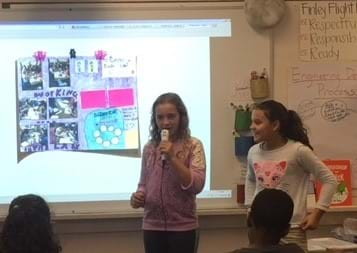 Two female fifth graders stand at the front of the classroom. The one on the left is speaking into a microphone. They have their poster presentation illuminated and hung on the board. The poster has pictures and writing, and is visually appealing. Other students sit and listen.