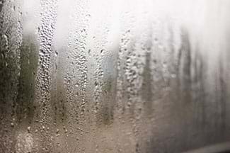 Image of water droplets forming on a window. Someone has touched the water droplets and there are finger streaks going through the water.