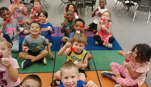 Fifteen kindergartner students sit on colorful mat eating red popsicles.