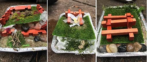 An image of student teams' designs using the provided materials: toy logs, rocks, moss, an aluminum pan, and sand.
