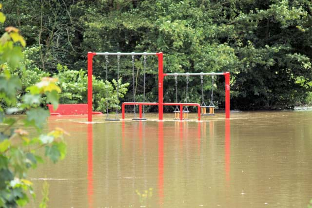 An image of a children's playground set under several feet of water.